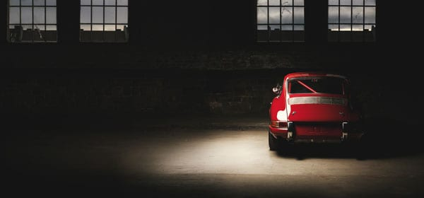 Feature a Porsche in a spot light within a warehouse